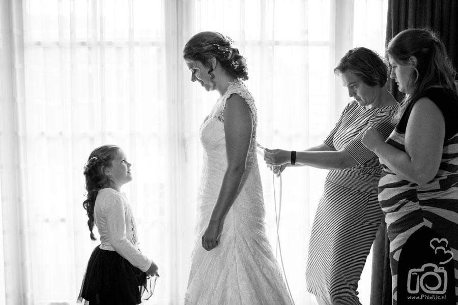 bruidsfotograaf groningen aankleden bruid inrijgen bruidsmeisje
